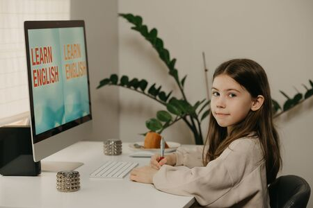 Distance learning. A young girl with long hair studying remotely online. A pretty female child learns a lesson using an all-in-one computer at home. Home education.
