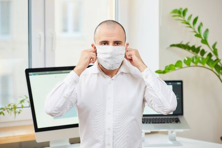 A man in a white shirt taking off a medical face mask against the coronavirus (COVID-19). An office worker at his workspace with computers and green plants in the background. Coronavirus quarantine.