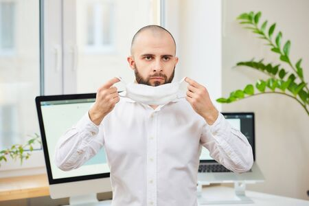 A man with a beard in a shirt putting on a medical face mask against the coronavirus (COVID-19). A manager at his workspace with computers and green plants in the background. Coronavirus quarantine.