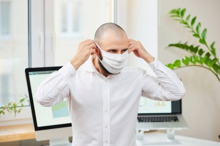 A man with a beard in a shirt putting on a medical face mask against the coronavirus (COVID-19). An engineer at his workplace with computers and green plants in the background. Coronavirus quarantine.