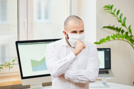 A man in a medical face mask against the coronavirus (COVID-19) strongly coughing into his fist. A manager at his workspace with computers and green plants in the background. Coronavirus quarantine.