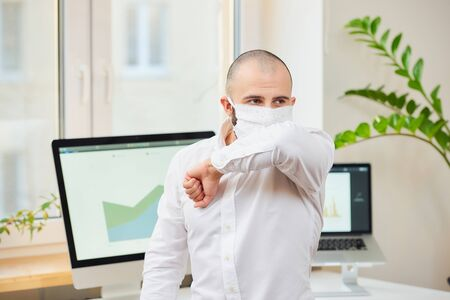 A man in a medical face mask against the coronavirus (COVID-19) coughing in the bend of his elbow. A manager at his workspace with computers and green plants in the background. Coronavirus quarantine. Reklamní fotografie