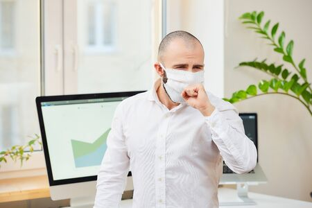A man in a medical face mask against the coronavirus (COVID-19) coughing into his fist. An office worker at his workspace with computers and green plants in the background. Coronavirus quarantine. Reklamní fotografie