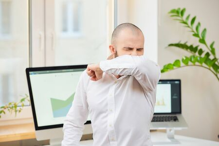 A man in a white shirt with a beard coughing in the bend of his elbow. A manager at his workspace with computers and green plants in the background. Coronavirus (COVID-19) quarantine.