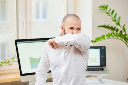 A man in a white shirt with a beard strongly coughing in the bend of his elbow. An office worker at his workspace with computers and green plants in the background. Coronavirus (COVID-19) quarantine.
