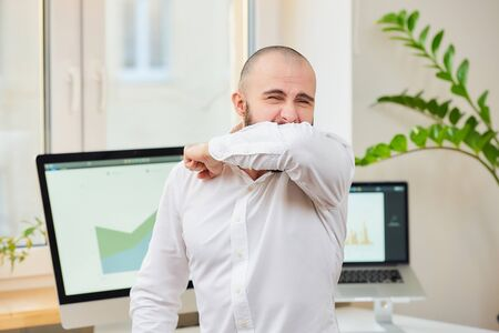 A man in a white shirt with a beard strongly coughing in the bend of his elbow. An office worker at his workplace with computers and green plants in the background. Coronavirus (COVID-19) quarantine.