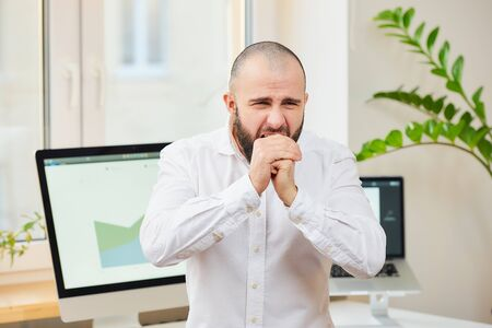 A man in a white shirt with a beard strongly coughing into his fists. An office worker at his workspace with computers and green plants in the background. Coronavirus (COVID-19) quarantine. Reklamní fotografie