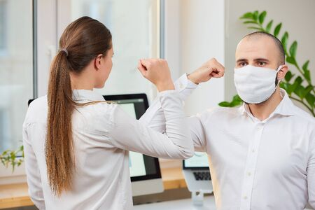 Elbow greeting to avoid the spread of coronavirus (COVID-19). A man with a medical face mask and a girl meet in an office with bare hands. Instead of greeting with a hug or handshake, they bump elbows Reklamní fotografie