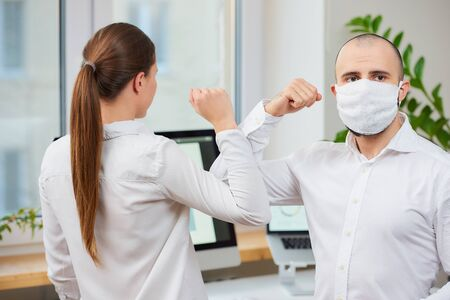 Elbow greeting to avoid the spread of coronavirus (COVID-19). Man with a medical face mask and woman meet in an office with bare hands. Instead of greeting with a hug or handshake, they bump elbows