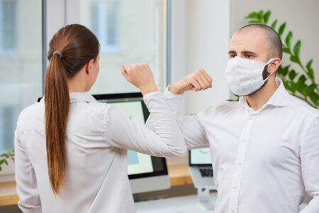 Elbow greeting to avoid the spread of coronavirus (SARS-CoV-2). Man with a medical face mask and woman meet in an office with bare hands. Instead of greeting with a hug or handshake, they bump elbows