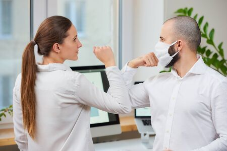 Elbow greeting to avoid the spread of coronavirus (2019-nCoV). Man with a medical face mask and woman meet in an office with bare hands. Instead of greeting with a hug or handshake, they bump elbows
