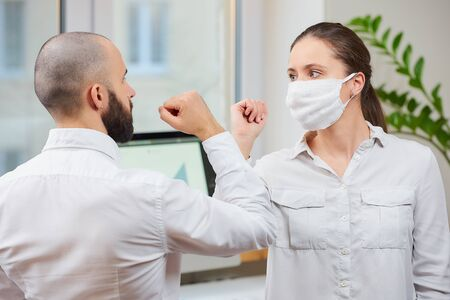 Elbow greeting to avoid the spread of coronavirus (2019-nCoV). Girl with a medical face mask and man meet in an office with bare hands. Instead of greeting with a hug or handshake, they bump elbows Reklamní fotografie
