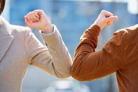 A close-up photo of elbow bumping. Elbow greeting to avoid the spread of coronavirus (COVID-19). A man and a woman meet with hands. Instead of greeting with a hug or handshake, they bump elbows.