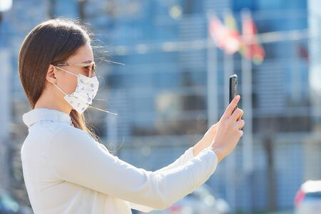 A woman using a smartphone wears a medical face mask to avoid the spread of coronavirus in the street. A close-up photo of a lady in sunglasses with a surgical mask on the face against COVID-19.