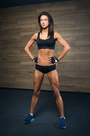 A sporty girl in a black short top, shorts, and gloves is posing in a gym. A female bronzed skin coach is waiting for a Crossfit training with a wooden wall on the background.