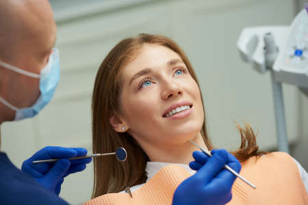 A smiling woman being examined by a male dentist in a medical face mask with a dental mirror and a dental explorer in a dental chair. A doctor treating a patient's teeth in a dentist's office.