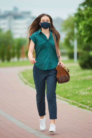 A pretty young woman in a navy blue medical face mask jumps holding a leather bag in the park. A girl is keeping social distance wearing a protective face mask to avoid the spread of coronavirus. Stock Photo