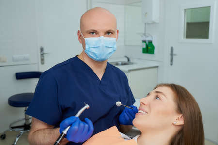 A dentist in a medical face mask holding a dental mirror and a drill poses before a procedure near a woman in the dental chair. A doctor and a female patient during treatment in a dentist's office