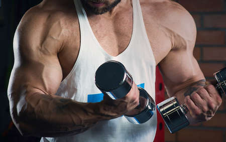 A close photo of arms of a bodybuilder who is doing biceps curls with dumbbells. A muscular shredded man with tattoos and a beard in a white tank top and blue shorts is training in a gym. 免版税图像