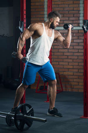 A shredded bodybuilder is doing biceps curls with dumbbells. A muscular man with tattoos and a beard in a white tank top and blue shorts is training near barbells lying on the floor in a gym.