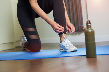 The hands and legs of a sporty girl in black tight suit who is tying her shoelaces on white sneakers while kneeling on the blue yoga mat near a green aluminum bottle of water before training at home. 写真素材
