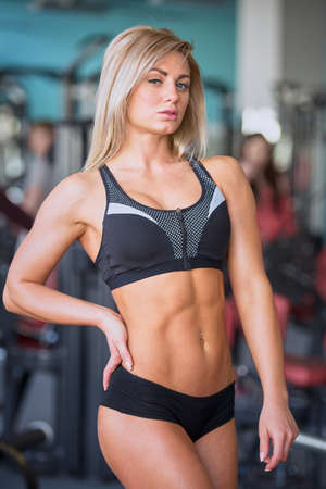A sporty young woman who wears a black short tight suit keeps her hand at a waist after a workout. A fitness blond girl is posing in a gym.