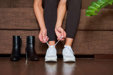 A close photo of the hands and legs of a sporty girl in black tights who is tying her shoelaces on white sneakers after took off ankle boots while sitting on the sofa before training at home.