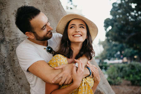 A smiling woman in a hat and a yellow dress and her happy boyfriend with beard are hugging under an old Valencian Ficus Macrophylla in Spain. A couple of lovers are enjoying Valencia in the evening.