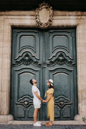 A girl in a hat and a dress with a plunging neckline and her boyfriend with a beard are staying near the giant doors holding each other's hand in the old town. A couple of tourists in Valencia.