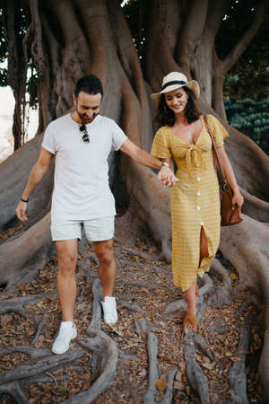 A young woman in a hat and a yellow dress and her boyfriend with a beard walk under an old Valencian Ficus Macrophylla in Spain. A couple of lovers are exploring Valencia in the evening.