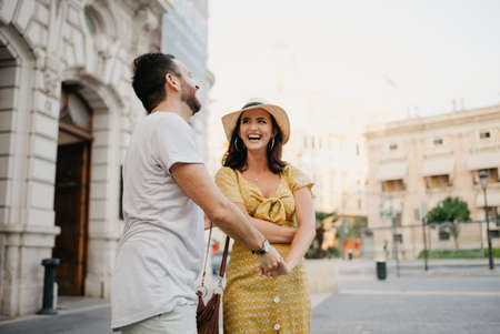 A laughing girl in a hat and a yellow dress with a plunging neckline is dancing with her boyfriend with a beard and sunglasses in the old town. A couple of tourists on the sunset in Valencia.
