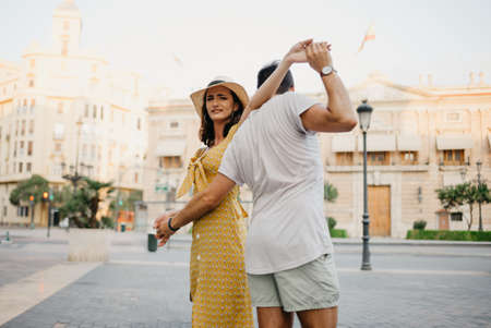 A happy girl in a hat and a yellow dress with a plunging neckline is dancing with her boyfriend with a beard and sunglasses in the old town. A couple of tourists on the sunset in Valencia.