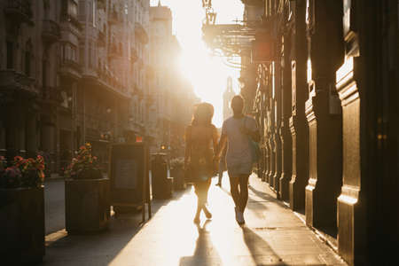 A girl in a hat and a yellow dress with a plunging neckline and her boyfriend with a beard are walking holding each other's hand in Spain. A couple of lovers on a date on the sunset in Valencia.