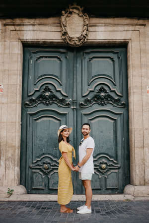 A happy girl in a hat and a dress with a plunging neckline and her boyfriend with a beard are posing near the giant doors holding each other's hand in the old town. A couple of tourists in Valencia.