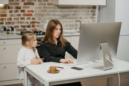 A mother is working remotely at home while a daughter is watching it. A businesswoman is working from an apartment near her blonde child.