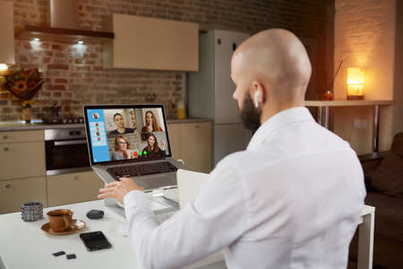 Back view of a male employee in earphones who is explaining and gesticulating on a business video conference on a laptop. A bald man with a beard on an online meeting with his colleagues at home
