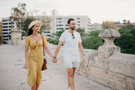 A girl in a hat and a yellow dress with a plunging neckline and her boyfriend with a beard are walking over the ancient bridge in old Spain town. A couple of tourists on a date in Valencia