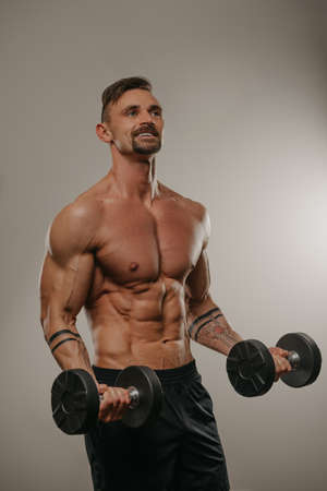 A muscular man with a beard is doing bicep curls with dumbbells. An athletic guy is demonstrating his sporty torso. An athlete with tattoos on his forearms is training his arms
