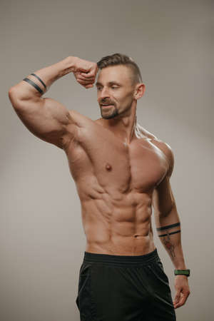 A smiling muscular man with a beard is posing after a workout. The athletic guy with tattoos on his forearms is demonstrating his big biceps.