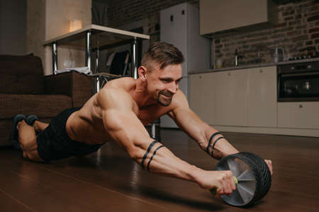 A muscular man with a naked torso is doing an abs workout in his apartment in the evening. A smiling bodybuilder with tattoos on his forearms is training with an ab wheel at home. Standard-Bild