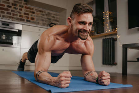 A happy muscular man with a naked torso is doing a plank on a blue yoga mat in his apartment in the evening. A smiling athletic guy with tattoos on his forearms is training at home. Standard-Bild