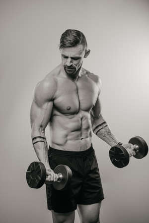 A black and white photo of a muscular man with a beard who is doing bicep curls with dumbbells. An athletic guy is demonstrating his sporty torso. An athlete is training his arms