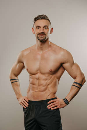 A muscular man with a beard is posing. The athletic guy with tattoos on his forearms is demonstrating his sporty physique. A smiling bodybuilder is relaxing after hard training. Standard-Bild