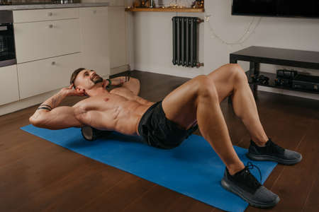 A muscular man with a naked torso is doing a myofascial massage to himself with a roller on a yoga mat in his apartment in the evening. A bodybuilder with tattoos on his forearms is training at home. Standard-Bild
