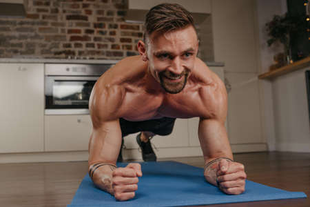 A muscular man with a naked torso is doing a plank on a blue yoga mat in his apartment in the evening. A smiling athletic guy with tattoos on his forearms is training at home.