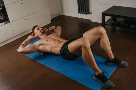 A photo from above of a muscular man with a naked torso who is doing a myofascial massage to himself with a roller on a blue yoga mat. A bodybuilder with tattoos on his forearms is training at home. Standard-Bild