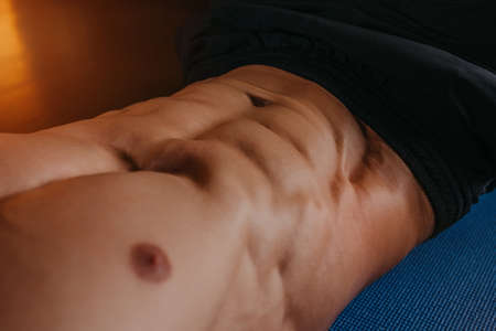 A close photo of the abs of a bodybuilder during doing crunches on a blue yoga mat.