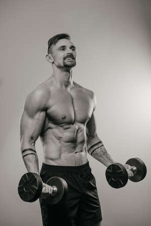 A black and white photo of a muscular man with a beard who is doing bicep curls with dumbbells. A smiling athlete with tattoos on his forearms is training his arms Standard-Bild