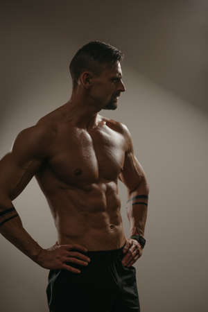 A high contrast photo of a muscular man with a beard who is posing. The athletic guy is demonstrating his physique. A bodybuilder with tattoos on his forearms is standing with his hands on his hips