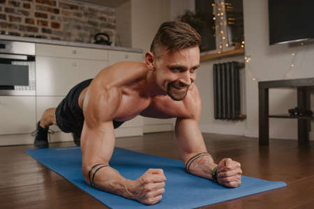 A happy muscular man with a naked torso is doing a plank on a blue yoga mat in his apartment in the evening. A smiling bodybuilder with tattoos on his forearms is training at home.